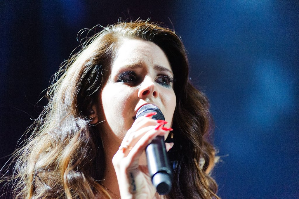 A close-up image of Lana Del Rey, a white woman with long, wavy brown hair and golden highlights. She holds the microphone close to her face as she sings, looking off into the distance. She wears heavy black eyeliner and bright red false nails. The background is various shades of blue.