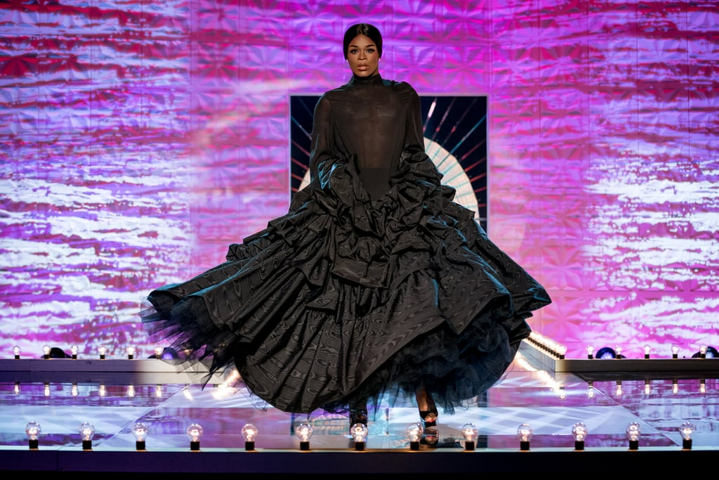 Asttina Mandella takes to the runway as Naomi Campbell, in a large flowing black dress, her hair scraped back in a bun. She stares directly at the camera, her mouth slightly parted. She looks assertive and confident; fierce.