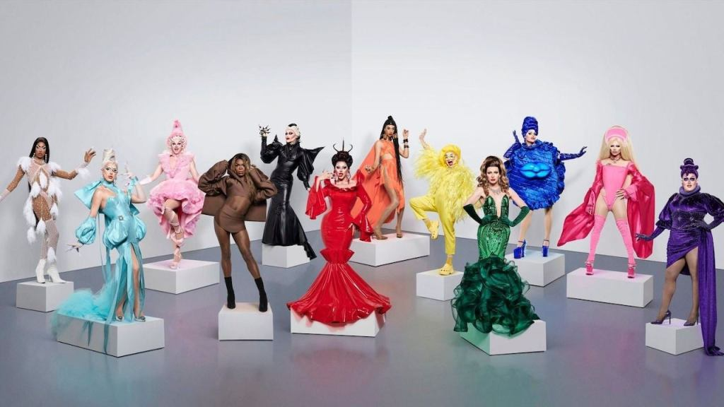 The twelve Drag Race contestants pose on white plinths. Each queen is wearing a bold monochrome outfits, each a different colour of the rainbow, and striking a fierce pose.
