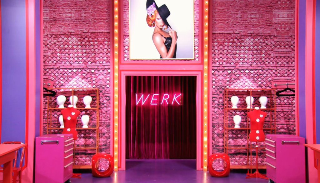 We see the Werk room entrance, entirely pink from ceiling to floor. Either side of the door are symmetrical mannequins, pink cabinets, and shelves. The word 'WERK' is lit up in a florescent pink sign on the wall.