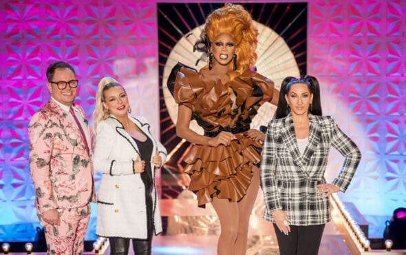 Ru and Michelle post on stage this week's guest judges Alan Carr and Sheridan Smith. Ru towers above the other three, a vision in brown: she wears a short ruffled dress, large dangling earrings, and a copper coloured wig.