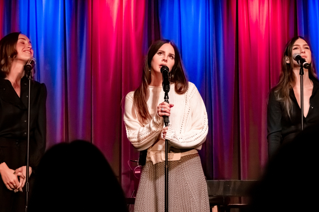 Lana Del Rey, a white woman with long straight brown hair, stands centre stage holding her microphone stand. Her mouth is open as she sings, and looks upwards. She wears a knitted cream jumper and a pattered skirt. Behind her is a theatre curtain, lit in alternating blue and pink light. On either side of her are two white women with brown hair, dressed all in black, who are her backing vocalists.