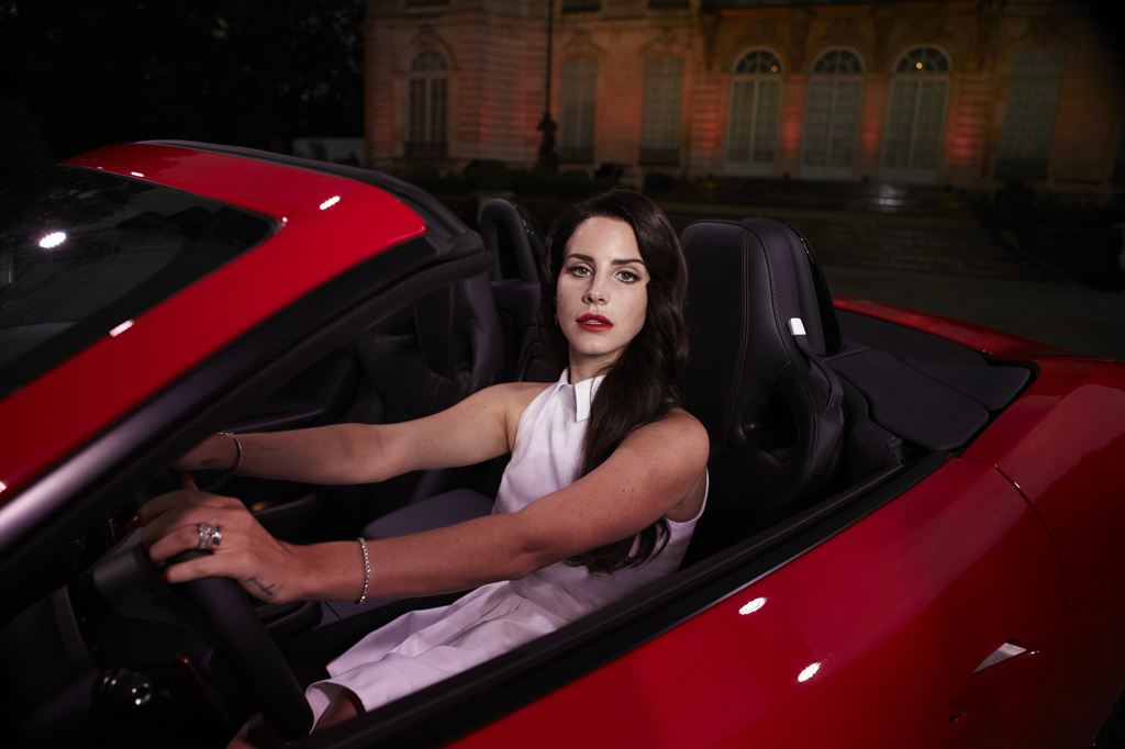 Lana Del Rey, a white woman with long brown hair and red lipstick, sits in the drivers seat of a convertible red sports car.  Lana wears a long white dress with a collar, bracelets and rings. She has her hands on the wheel, and is looking at the camera with a blank expression.