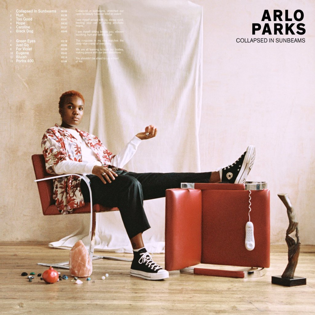 Arlo Parks' album cover for Collapsed in Sunbeams. Her outfit is youthful and fun, sporting black converse all stars and a hawaiian shirt. A collection of objects are scattered around her: A vintage wire phone, a salt crystal and a fallen leather chair, on which she's resting one leg.