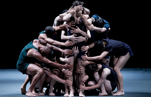 A group of dancers stand on a dark, bare stage. They wear dark shorts and t-shirts - in navy, grey and black. A dancer stands in the centre upright, surrounded by the rest of the ensemble, who place their hands all over them - including over the dancer's mouth, eyes and genitals.