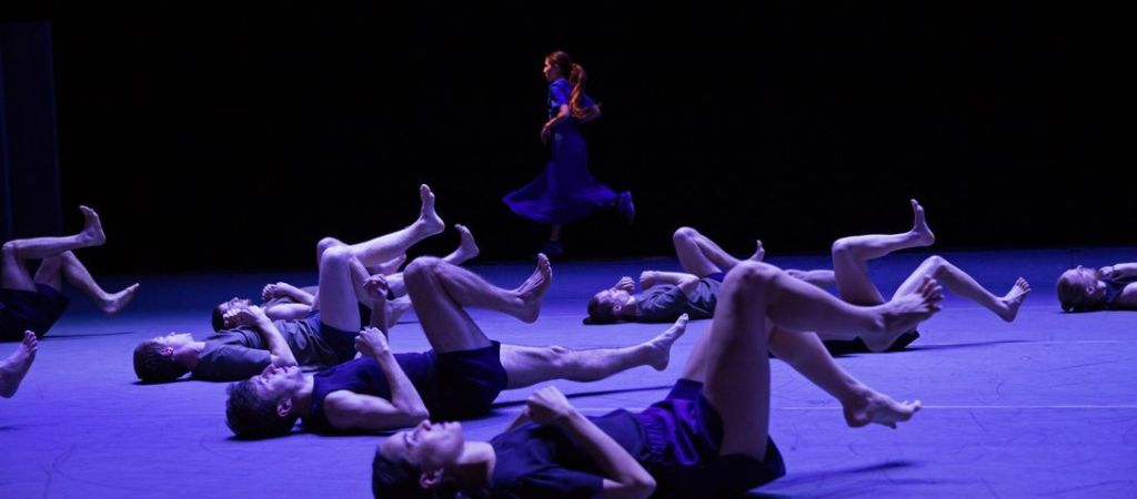 Ensemble of dancers lay on their backs on the floor of the stage, lit in blue and purple tones. They move their legs as if they are running. In the distance, we see a woman in a blue dress running upright on the spot - her long ponytail swishing.