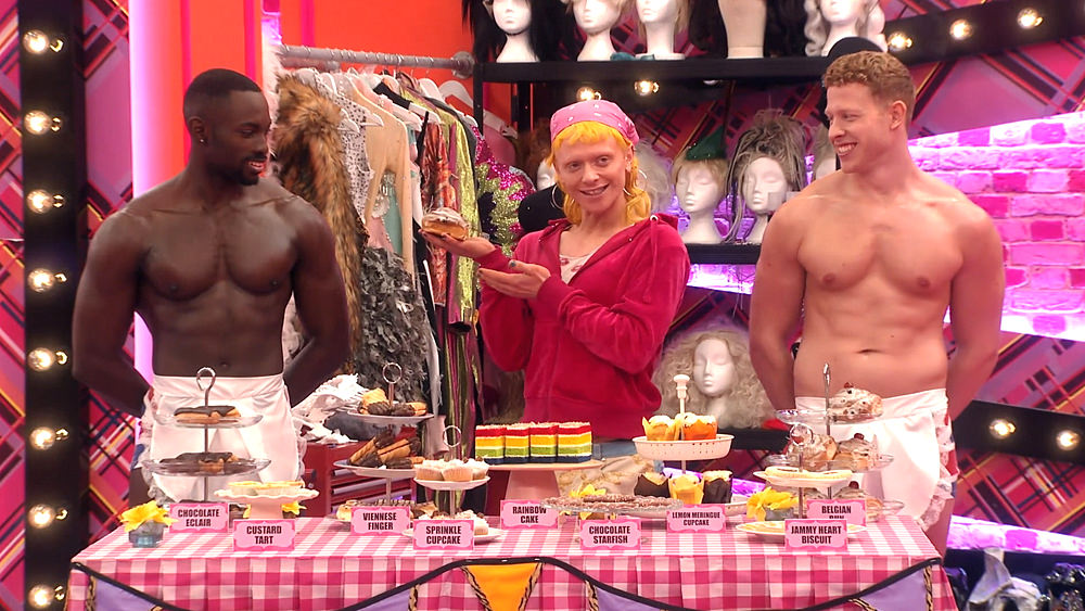 Bimini takes part in the 'bake off' mini challenge. She holds up an iced bun provocatively, topless members of the 'Brit crew' either side of her.