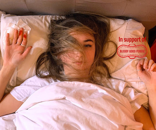 Cover image for the audio drama. The image is a photograph taken from above, featuring a girl laying in bed with matted hair and blood on her index and middle finger. She looks tired, the sun is shining on her face. The sheets are white.