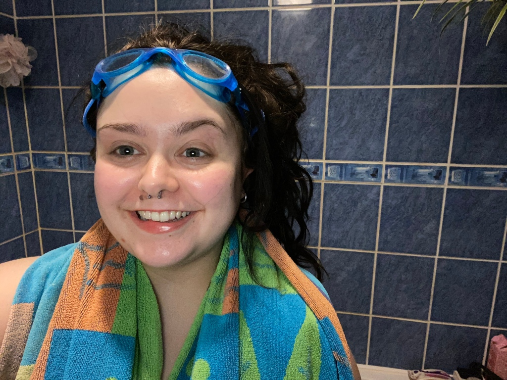 Abbie, a white woman, grins at the camera with a blue, green and orange beach towel around her shoulders. She has long, wavy brown hair which is piled on her head messily, pushed up by bright blue goggles. Behind her, we can see blue marble-effect tiled and a pink shower scrub.