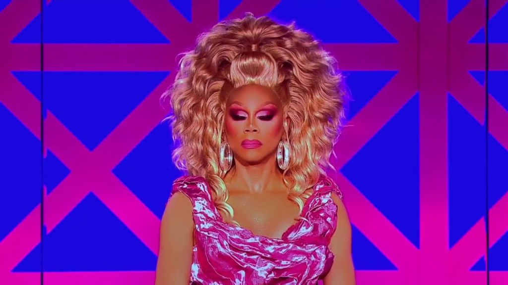 Ru sits on the judging panel, dressed in a pink ruffled dress and big, blond hair. Her heavily made up eyes are closed, as if contemplating. She does not seem impressed.