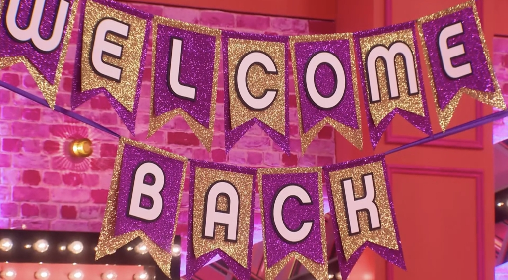 A sparkly 'welcome back sign' is hung in the werk room for the queens on their return.