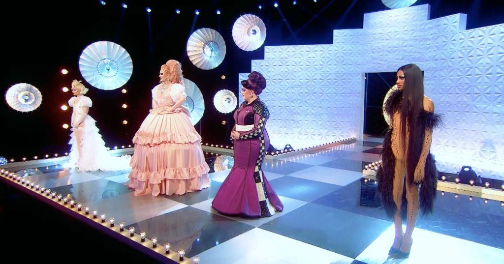 The four queens stand on the runway in their final runway outfits. Bimini is dressed in a floor length white 'East London bride' take on a wedding dress, Ellie in a big, pink hoop skirt with matching hair, Lawrence in a fitted, aubergine coloured gown and Tayce in a nude, feathered catsuit moment.