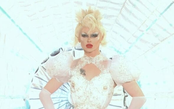 A close up of Bimini in her wedding dress final runway outfit. She wears elbow length white gloves, puffy white laces sleeves, and stunning makeup with big smokey eyes, red lips and short white-blonde hair.