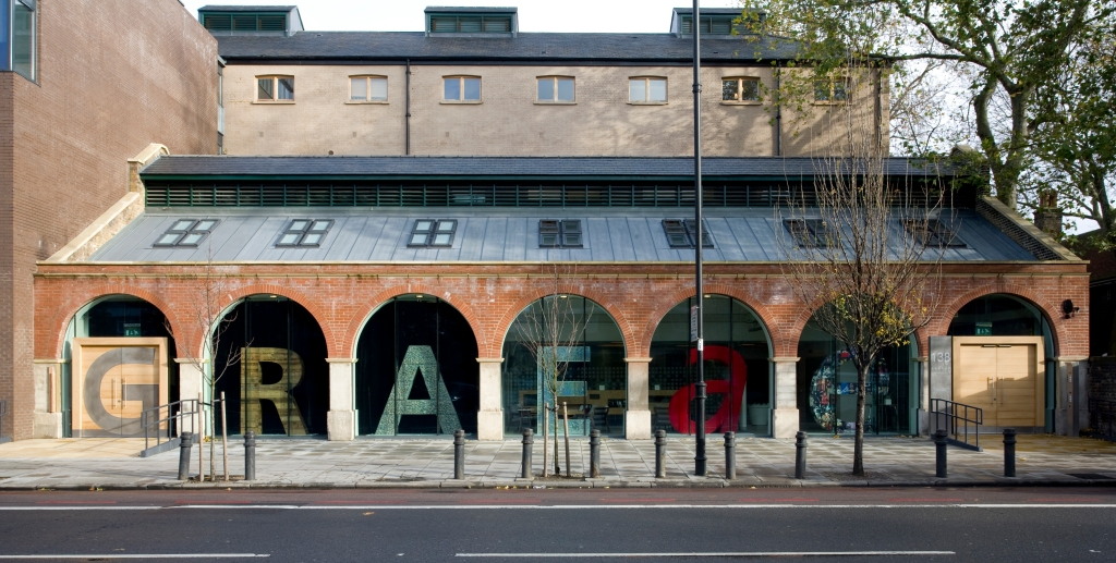 The Graeae centre in London with a very large sign made up of solid letters that spell Graeae. Each letter is under an archway outside the building.