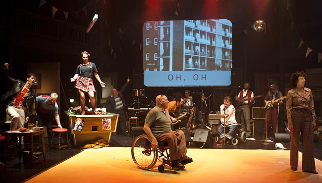 A photo from 'Reasons to be Cheerful', a theatre production. The scene features many people, including a band in the back, a woman dancing on a pool table, bunting and a disco ball. Front and centre is a man in a wheelchair singing his heart out.