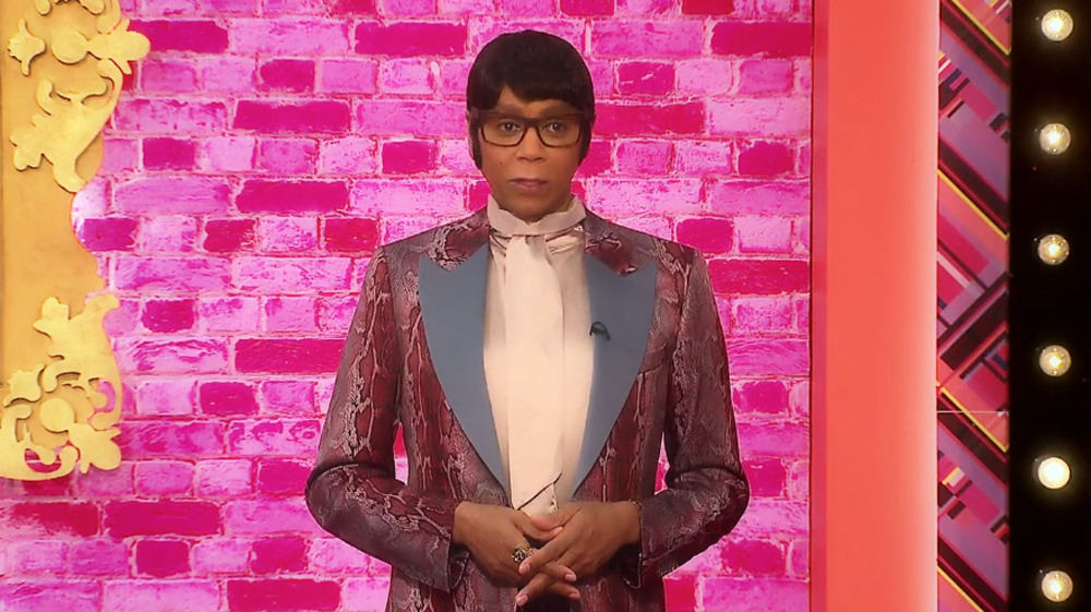 Ru in 'butch drag' wearing a short dark wig, glasses and a garish red 70s style suit. He looks serious, as he explains this week's challenge to the queens.
