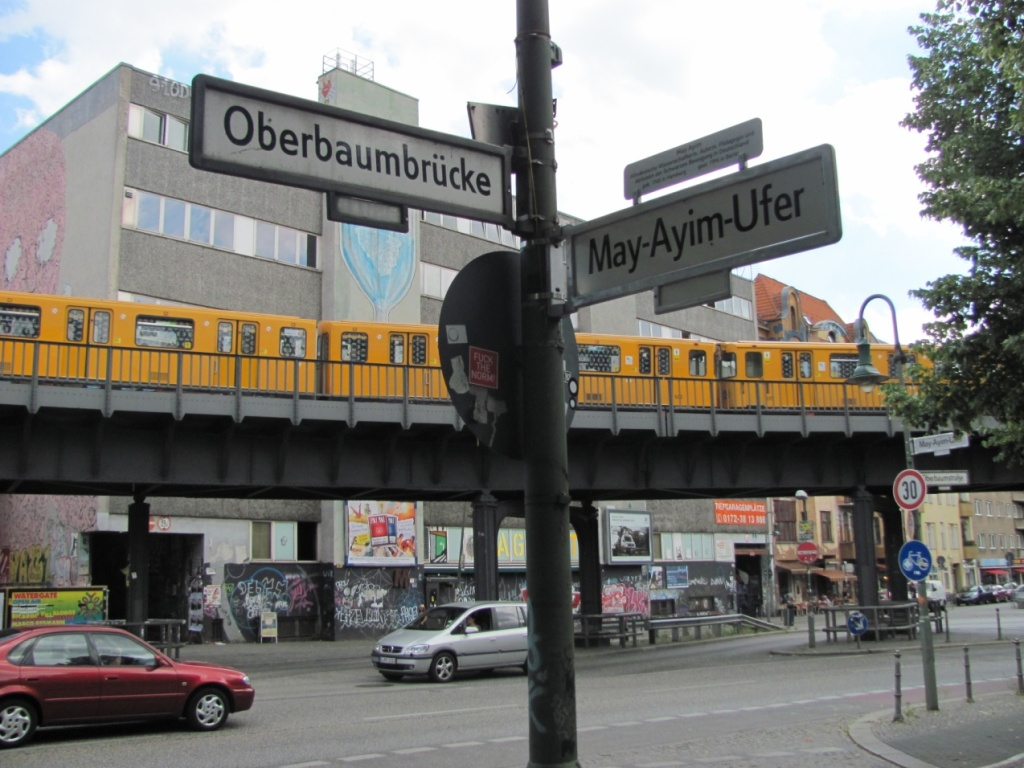 The street sign in Berlin, Kreuzberg in honour of May Ayim. Behind the street sign is a busy road and a bright yellow train trundling along on an overpass.