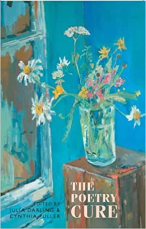 The cover of Julia Darling's 'The Poetry Cure' book. The cover design looks painted, with a wooden box in the bottom right and the pale pink title imposed over it. A glass vase sits on the box with white, yellow and pink flowers splaying off in all directions. The background is blue, with a window sivible to the left.