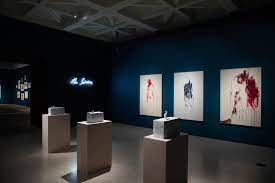 A shot of one of the rooms of the gallery. It is darkly lit, and we see three of Emin's large paintings on the wall, with three smaller sculptures on plinths in front of them.