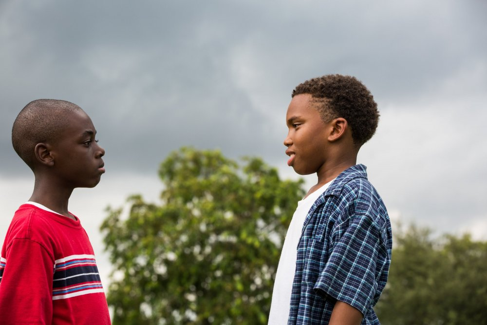 A scene from the film Moonlight. Child actors Alex Hibbert and Jaden Piner stand facing each other, against the backdrop of some trees and a dark, stormy sky.