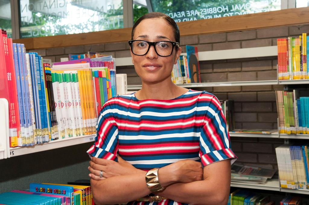 Zadie Smith poses in front of some book shelves, in what looks like a library. She is wearing a bright striped t shirt, and black glasses, her arms crossed and a slight smile on her face.