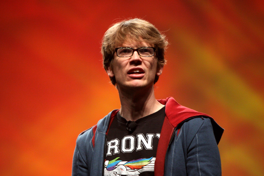 Hank Green, a thirty-something white man with glasses, is on stage at Vidcon 2012 in Anaheim, California. He is wearing a hoodies and a 'Brony' shirt.