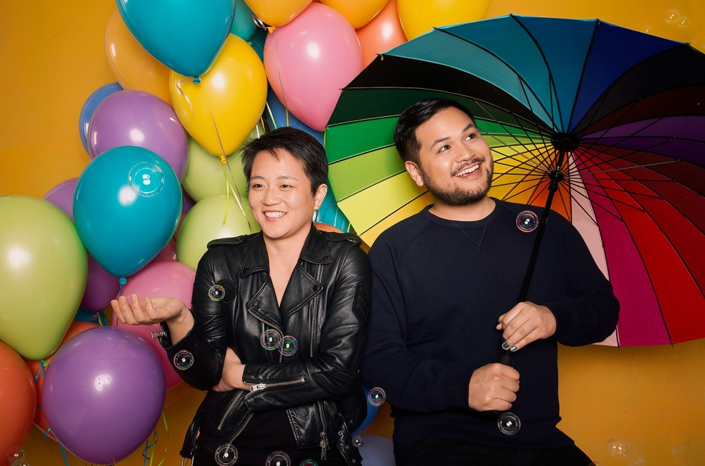 Tobin and Kathy stand in front of a yellow wall with rainbow balloons, bubbles and a rainbow umbrella. They are both dressed in black, and smiling.