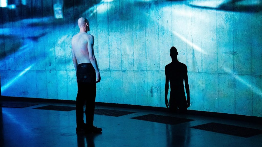 A man stands in front of his own shadow, cast against a wall; dappled in blue light.