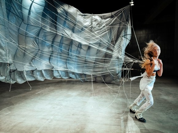 A still from one of the performance pieces. A woman is walking, a large blue parachute bailing out behind her. Her eyes are closed, and she is dressed all in white, with her blonde hair blowing out behind her.
