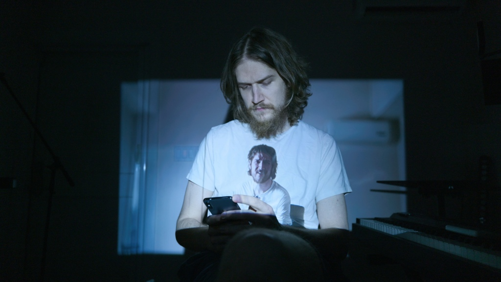 Bo Burnham is sat in front of the camera, looking down at his phone. He looks dishevelled and tired. His hair and beard are long. He is sitting in near darkness. A video of Bo from a few months earlier is being projected onto present-day Bo's chest. In the video being projected, Bo is looking at the camera. He looks less dishevelled than present day Bo.