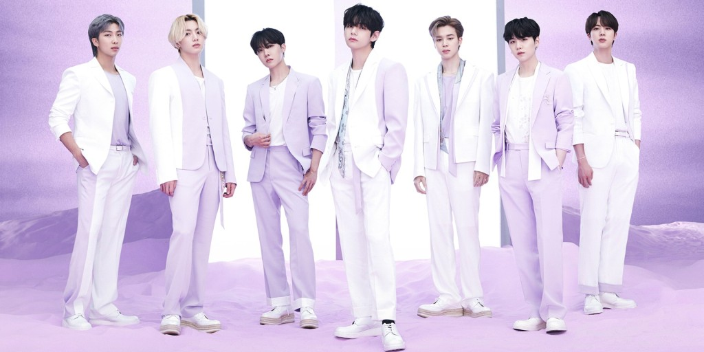 Album cover from 'The Best'. The band are all dressed in white and pale purple suits, with a purple background. They pose for the camera moodily.