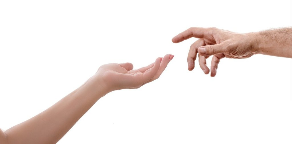 Two hands reaching for each other with a white background. The image is reminiscent of 'The Creation of Adam'  by Michaelangelo.