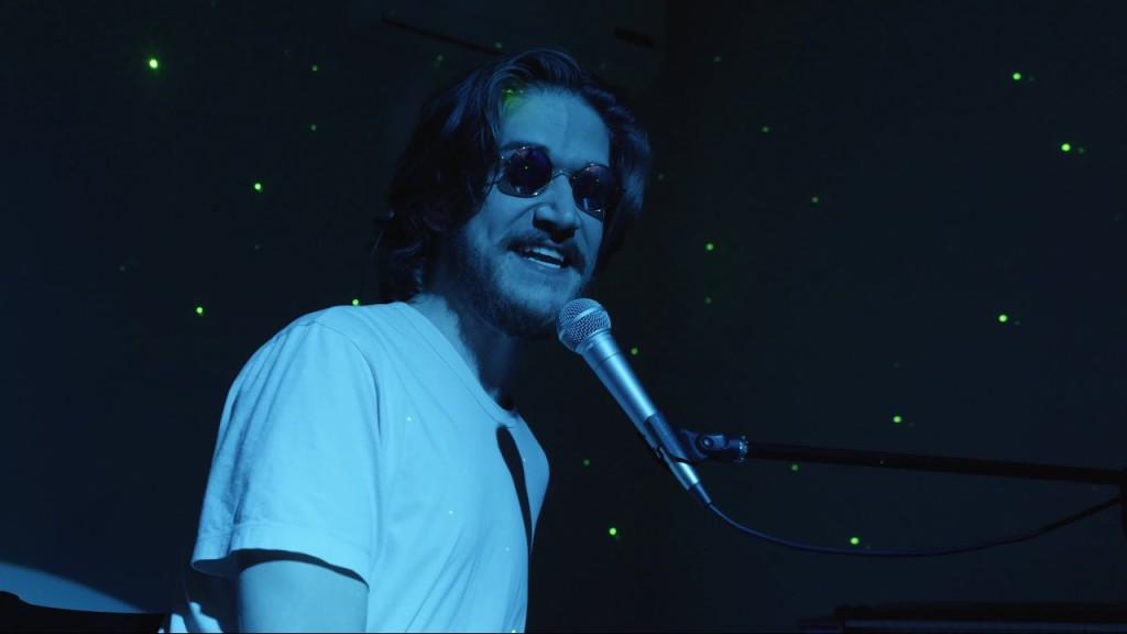 Bo Burnham faces the camera as he sings into a microphone. He is wearing sunglasses with round frames that make him look menacing. The background behind him is pitch-black, with just a few green dots illuminating it. Blue light washes over Burnham, adding to the sinister undertones of the image.