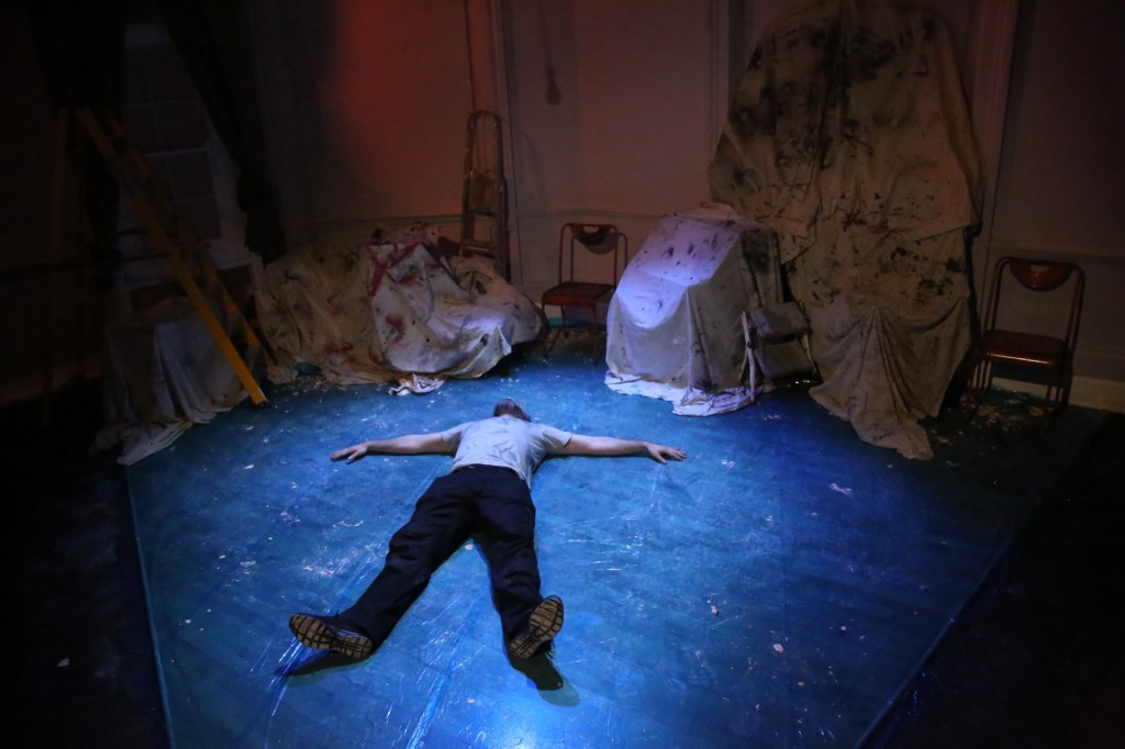 Padraig, a white man wearing a grey t shirt and black trousers, lays on his back on paint-splattered dark wood floor - arms and legs splayed out. Around him, we see paint-splattered sheets covering furniture, ladders, and white walls.