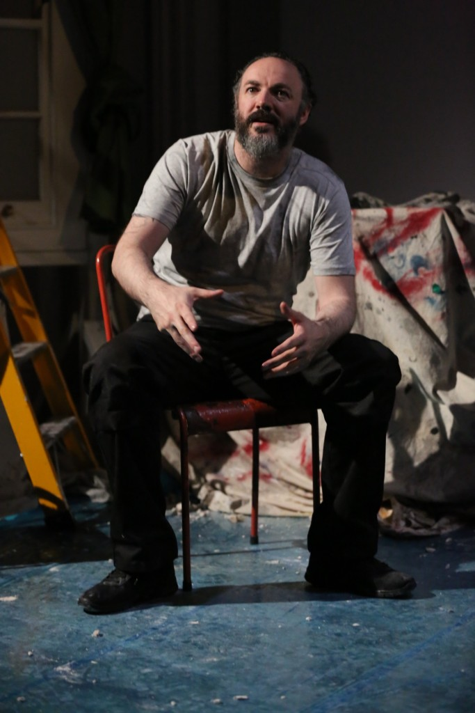 Padraig, a white man with a beard and slicked-back hair, sits on a red hair, gesturing with his hands as he speaks. Behind him, we see paint-splattered sheets covering furniture, and a yellow step ladder.