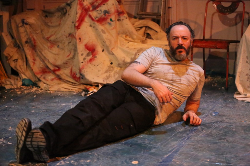 A bearded white man with dark, slicked back hair lays on a paint-splattered floor, resting on one arm nonchalantly. In the background, we can see bits of rubble and dirt, and a paint-covered sheet draped over furniture.
