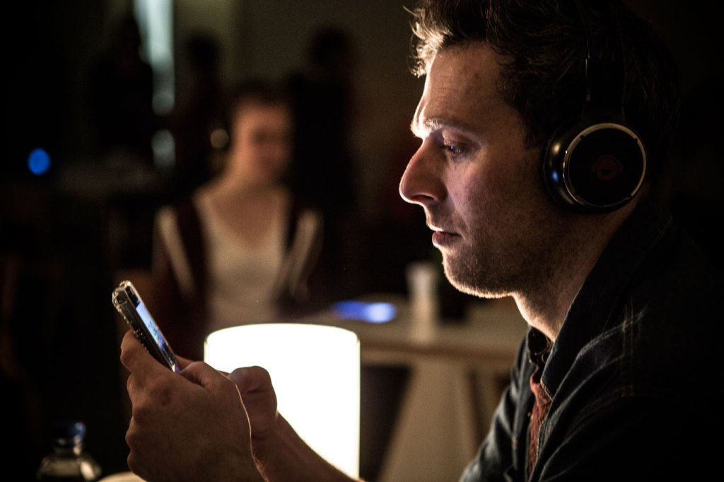 A medium build brunette man with stubble is sitting in a cafe. We view him from the side. There is a blurry figure of another cafe goer at the table behind him. Both people are wearing headphones. The man is staring intently at his phone which is clutched between both hands. His thumbs are poised over the screeen.