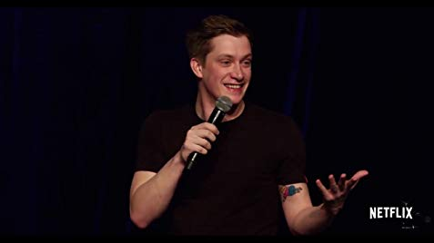 Comedian Daniel Sloss, a white man with short-ish mousy hair, holds a microphone to his mouth and gestures with his left hand upturned. He is smiling, and slightly flustered.