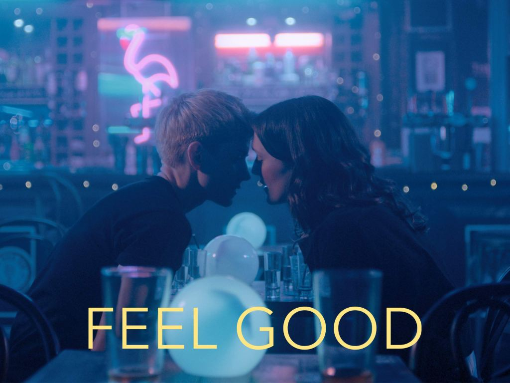 Mae and George sit at a table in a bar softly lit with twinkling lights and a blue haze. They are leaning in, foreheads nearly touching, lips parted, entirely enraptured by one another. At the bottom of the image is the title of the show - Feel Good - in white lettering.