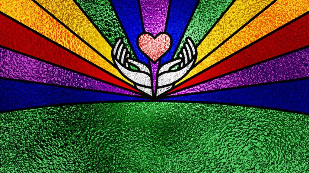 A stained glass window. There is a heart in the centre being cradled by two hands. The top half of the window is split into coloured beams. They are in shades of the rainbow.