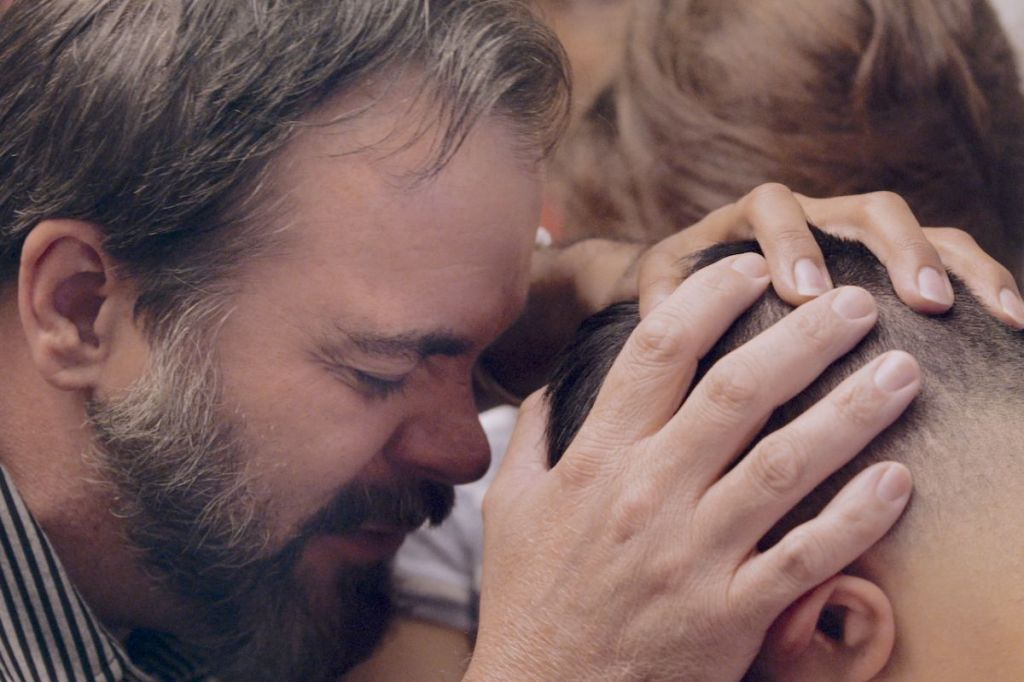 A still from the film. A man is grasping the head of someone else, with another in the background. His eyes are closed in prayer.