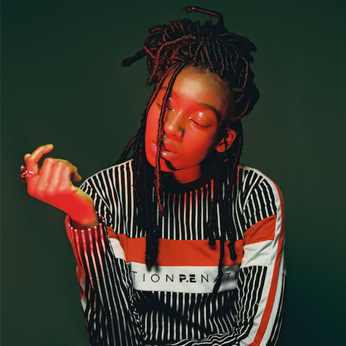 Little Simz, a black woman with braids, is lit in red. She is wearing a black stripy shirt and looking at her wrist as though inspecting her sleeve.