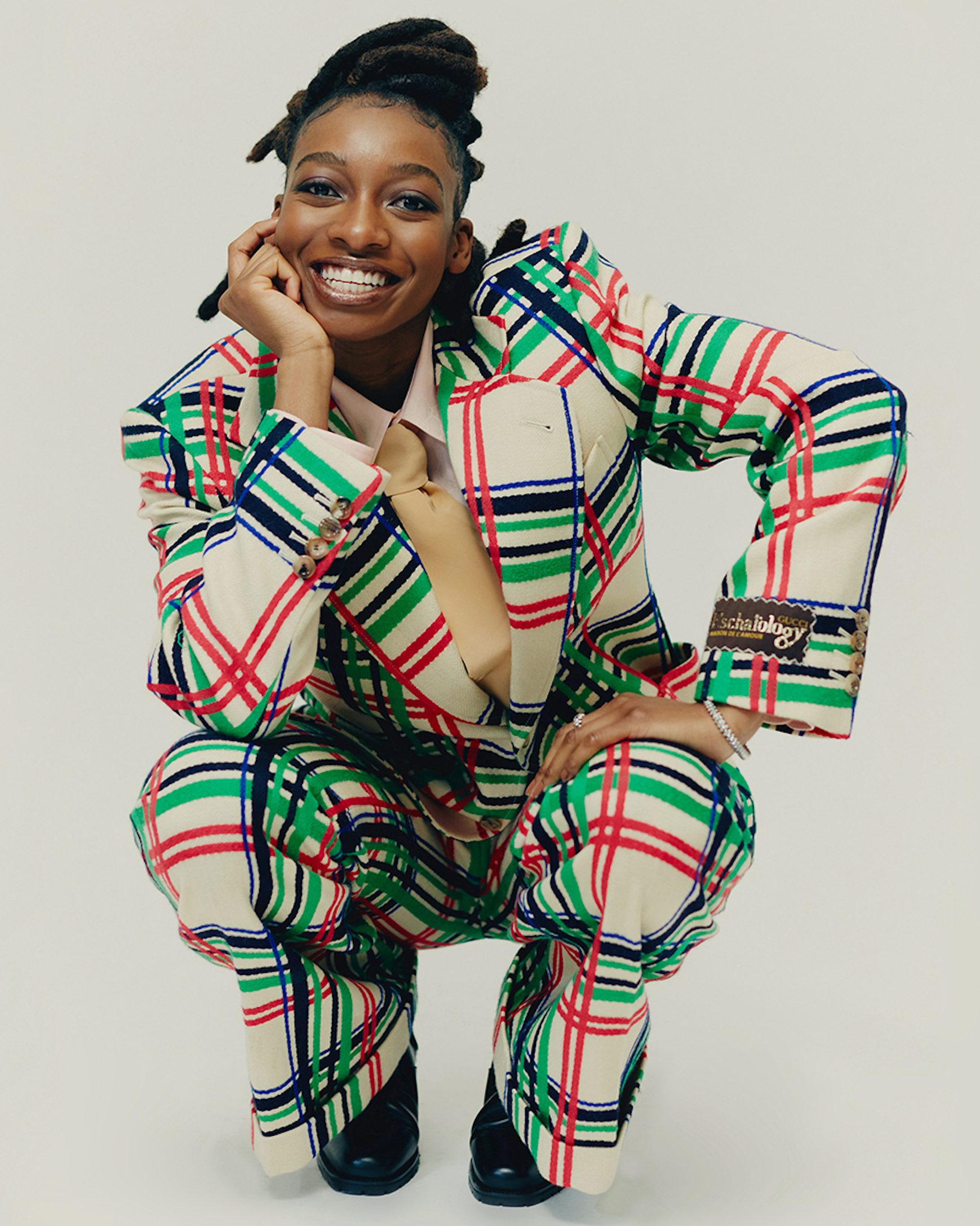 Little Simz is crouching down and smiling at the camera. She is wearing a cream suit with a black, bright red and green check pattern.
