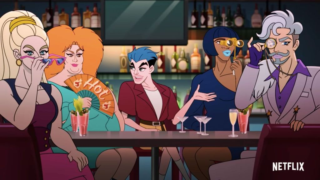 Twink sits at a table with his drag queen friends, talking enthusiastically. The drag queens are all looking at someone off screen. They look fabulous, extravagant and ready to hop on stage.