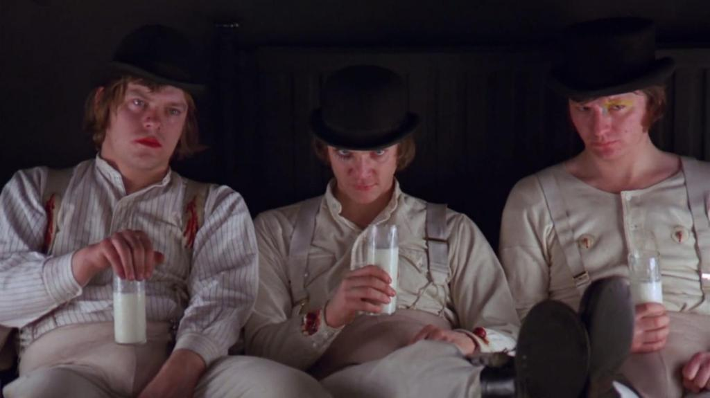 Alex and his Droogs sit on black, high backed bench seating. Alex stares intensely at the camera, wearing a black bowler hat, his long eyelashes stylised and black over one eye. He holds up a glass of milk, and looks menacing. His Droogs wear similar attire with varying make up, and look away from the camera with their milk in hand, looking sad.